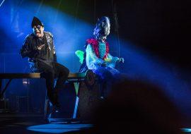 Scena oświetlona niebieskim światłem, na wielkiej huśtawce siedzą mężczyźni przebrani za czarnego i kolorowego ptaka w czapce z piórami. Czarny odwraca głowę i wystawia język.