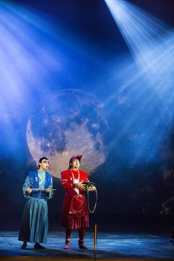 Scena oświetlona na niebiesko. Na niej stoi dwóch mężczyzn. Jeden ubrany w długi, niebieski kostium. Drugi w czerwony. Za nimi w tle duża kula na która padaja białe promienie światła.