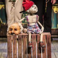 Na środku, na drewnianej skrzynce siedzi drewniana lalka w spodenkach w kratkę i czerwonej czapce. Obok leży maska. W tle dwie osoby trzymające róże.