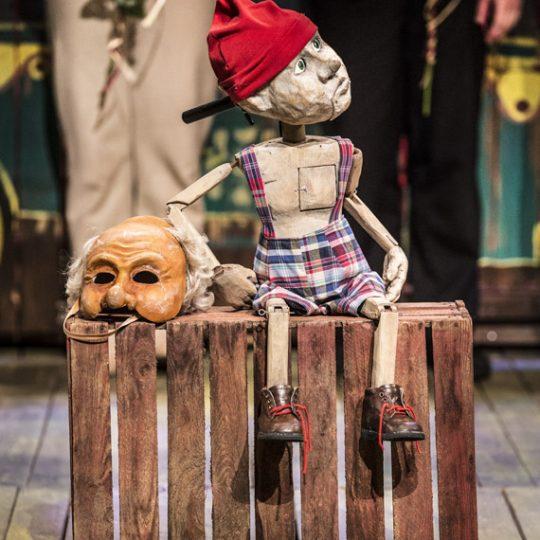 Na środku, na drewnianej skrzynce siedzi chłopiec z drewna w spodenkach w kratkę i czerwonej czapce. Obok leży maska. W tle dwie osoby trzymające róże.