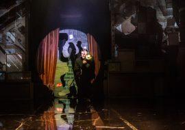 Na scenie stoi pochylony mężczyzna który trzyma lampę. Za nim, na tle strumienia światła , który tworzy koło, widać cień postaci w czapce.