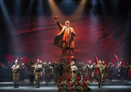 Na scenie mężczyźni i kobiety w mundurach. Tyłem do widowni siedzą cztery kobiety , w rękach trzymają pdniesione do góry kwiaty. Dalej w jednym rzędzie, kilku mężczyzn trzyma oparte na ramionach flagi w kolorze czerwonym. Za nimi grupa mężczyzn, wszyscy stoją na baczność trzymając dłonie przy skroni w geście salutowania. Na końcu, na środku, pomnik Lenina trzymającego dłoń w górze.