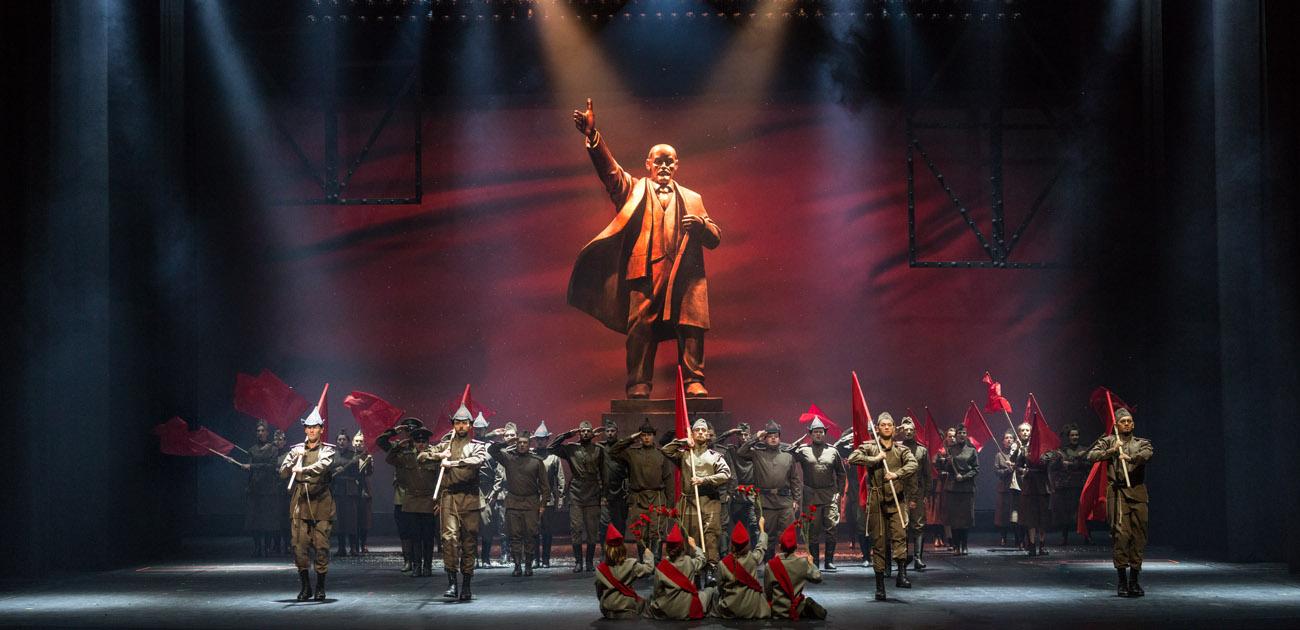Na scenie mężczyźni i kobiety w mundurach. Tyłem do widowni siedzą cztery kobiety, w rękach trzymają pdniesione do góry kwiaty. Dalej , w rzędzie kilku mężczyzn trzyma oparte na ramionach flagi w kolorze czerwonym. Za nimi grupa mężczyzn, wszyscy stoją na baczność  trzymając dłonie przy skroni w geście salutowania. Wśród nich kilka kobiet z flagami w kolorze czerwonym. Na końcu, na środku, pomnik Lenina trzymającego dłoń w górze.