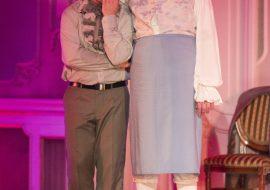 Na scenie dwóch mężczyzn. Jeden z nich, w stroju kobiecym , trzyma ręke na głowie drugiego mężczyzny.