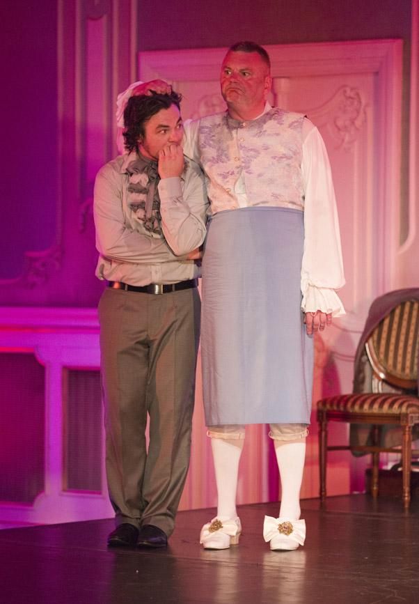 Na scenie dwóch mężczyzn. Jeden z nich, w spódnicy , trzyma ręke na głowie drugiego męzczyzny.