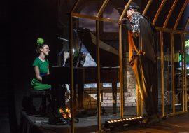 Z lewej strony kobieta w zielonym ubraniu gra na fortepianie. Przed nią mężczyzna w czarnym ubraniu wystawia głowę z wielkiej złotej klatki. Z prawej strony mężczyzna w zielonym ubraniu gra na instrumentach perkusyjnych.