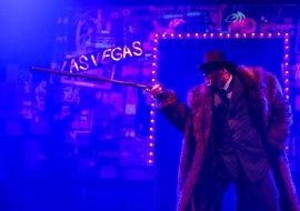 """Scena oświetlona niebieskim światłem. Na środku stoi mężczyzna w garniturze i futrze, w ręku trzyma laskę. W oddali widać podświetlony napis """" Las Vegas"""""""