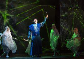 Na środku stoi mężczyzna w niebieskim, długim kostiumie. Wokół niego tańczy kilka kobiet w białych, zwiewnych sukienkach. W tle iluminacja świetlna z zielonych linii.