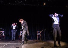 Na scenie trzech mężczyzn w białych koszulach i czarnych frakach. Stoją w pewnej odległości od siebie, trzymając się za uszy. Pomiędzy nimi trzy krzesła.