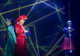 Na scenie trzy osoby. Po lewej kobieta w niebieskim kostiumie i mężczyzna ubrany na czerwono, stoją odwróceni do siebie plecami. Po prawej stronie mężczyzna trzyma w rękach przedmiot przypominający dzidę. W tle iluminacja świetlna w postaci linii ułożonych w różnych kierunkach.