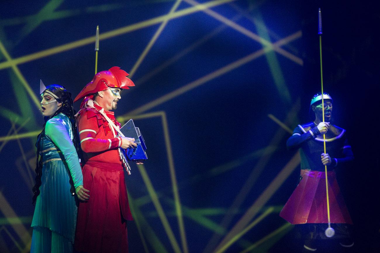 Na scenie trzy osoby. Po lewej kobieta w niebieskim kostiumie i mężczyzna ubrany na czerwono, stoją odwróceni  do siebie plecami. Po prawej stronie mężczyzna trzyma w rękach przedmiot przypominający dzidę. W tle