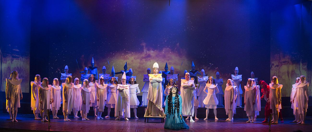 Na scenie kilkadziesiąt osób w mitycznych kostiumach. Na środku, na kolanach, stoi kobieta w niebieskim stroju. Za nią , na podeście stoi męzczyzna, ze skrzyżowanymi rękami na piersi.
