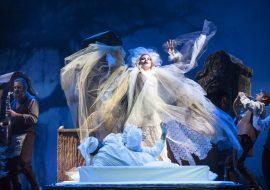 Na środku łóżko. Na nim kobieta i mężczyzna w białych strojach. Nad nimi kobieta z białymi włosami i rozwianej, tiulowej sukni. Po obydwu stronach mężczyźni, grający na instrumentach.