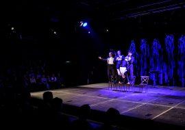 Scena oświetlona niebieskim światłem. Na scenie czterech mężczyzn we frakach, stojących na krzesłach. Dwóch z nich , trzyma za nogi mężczyznę stojącego na rękach. Widownia w półmroku.