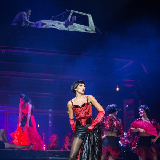 Na pierwszym planie kobieta w czerwono-czarnym kostiumie. Za nią, po prawej stronie dwie kobiety, w czerwono-czarnych kostiumach hiszpańskich, z wachlarzami w dłoniach. Za nimi, na podwyższeniu kobieta w długiej, czerwonej sukience z falbanami.Na dachu, nad sceną mężczyzna, obok niego widoczna część samochodu.