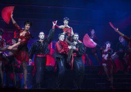 Grupa kobiet i mężczyzn w czerwono-czarnych hiszpańskich kostiumach tańczy na scenie. Na środku dwóch mężczyzn trzyma na ramionach kobietę. Po obydwu stronach, kobiety z rozłożonymi, czerwonymi wachlarzami.