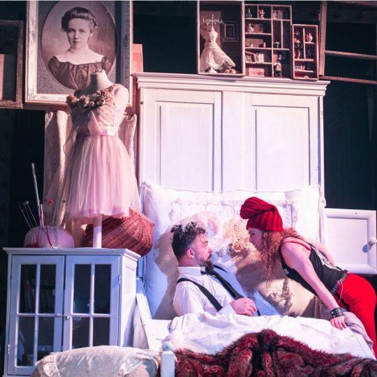 Mężczyzna elegancko ubrany siedzi na łóżku. Nad nim pochyla się kobieta w czerwonej czapce. Za nimi stoi biała szafa. Na szafce przy łóżku stoi pleciony koszyk i igielnik. Na małym manekinie krawieckim wisi sukienka.