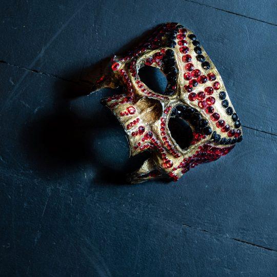 Na ciemnych deskach sceny leży złota maska w kształcie czaszki, ozdobiona czerwonymi i czarnymi kamykami