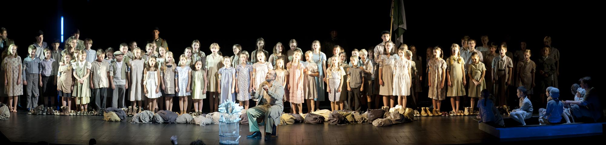Scena wypełniona dziećmi stojących w rzędzie. Za nimi kilku mężczyzn w mundurach. Na środku siedzi mężczyzna