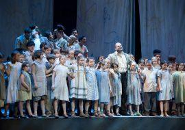 Na scenie mężczyzna w okularach i beżowym płaszczu. Wokół niego grupa dzieci. Dalej, po lewej stronie, grupa kobiet i mężczyzn rozmawiających ze sobą.
