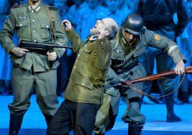 Scena oświetlona niebieskim światłem. Na pierwszym planie trzech mężczyzn. Dwóch w mundurach niemieckich i hełmach, z karabinami. Jeden stoi wyprostowany patrząc przed siebie. Drugi uderza karabinem w plecy mężczyznę ubranego w marynarkę od munduru. Za nimi stoi grupa dzieci. Przodem do nich stoi mężczyzna z karabinem.