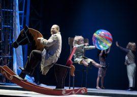 Na pierwszym planie mężczyzna w okularach i beżowym płaszczu. Siedzi na drewnianym, bujanym koniu. Dalej, na wysokim krześle siedzi mężczyzna i rzuca kolorową, plażową piłką. W oddali stoją dwie kobiety z rękami uniesionymi do góry w swoją stronę.