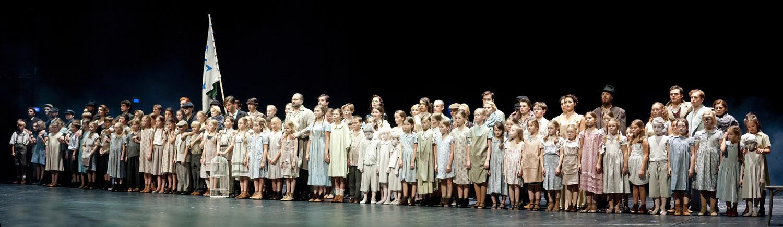 Na scenie kilkadziesiąt osób. Na przodzie, w rzędzie wzdłuż sceny, grupa dzieci. Pomiędzy nimi mężczyzna w okularachi beżowym płaszczu. Przed nimi, na środku, pusta klatka. Dalej kilka kobiet i mężczyzn.Jeden z nich trzyma dużą flagę z niebieską gwiazdą Dawida. Wszyscy patrzą przed siebie.