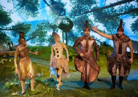 Na polanie cztery osoby w strojach w postaci instrumentów muzycznych: puzonu, fletu i kontrabasów. W tle korony drzew.