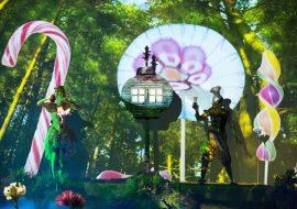 Na tle lasu stoją dwie postacie w kostiumach w formie instrumentów - puzonu i fletu. Pomiędzy nimi duże, kolorowe lizaki.