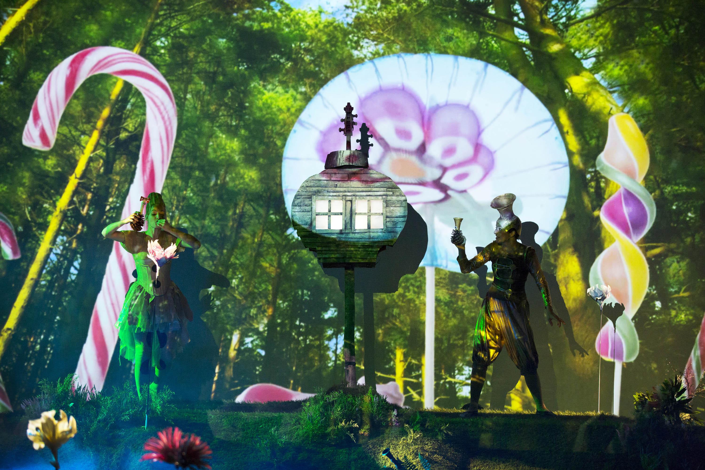 Dwie postacie w bajkowych kostiumach stoją na tle lasu. Pomiędzy nimi duże, kolorowe lizaki.