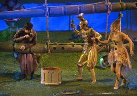 Na zdjęciu dwa duże , drewniane flety splecione sznurkami. Na jednym opiera się mężczyzna. Obok stoją dwie postacie w beżowych kostiumach w formie instrumentów: puzonu i fletu.