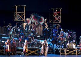 Na scenie drewniana konstrukcja z podestami, schodami i wieżyczkami. Na podestach stoja armaty. Za jedną z nich stoi mężczyzna w kostiumie księdza.Wszędzie stoją mężczyźni z szablami w dłoniach.