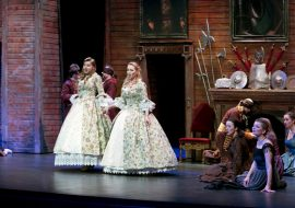 Dwie kobiety w długich , balowych sukniach stoją na środku sceny. Śpiewają. Po prawej i polewej stronie siedzą kobiety i mężczyźni