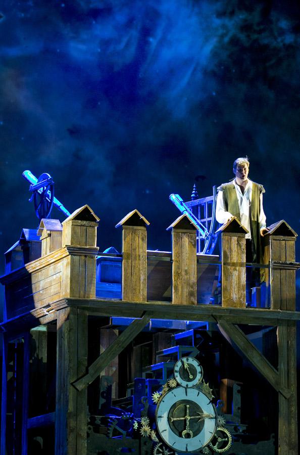Na drewnianej, szerokiej wieżyczce stoi mężczzyna. Pod nia widać duży zegar.
