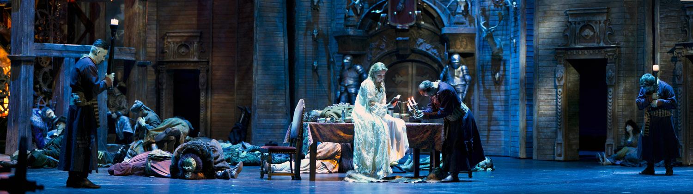 Na scenie duży stół. Na nim siedzi kobieta w białej, długiej sukni. Obok stoi mężczyzna pochylony nad stołem. Dookoła leży na scenie kilka osób