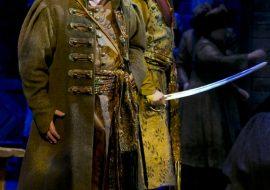 Na scenie dwóch mężczyzn, w strojach szlacheckich. Jeden z nich trzyma szablę. Obydwaj śpiewają.