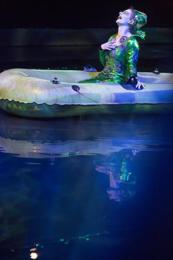 Na wodzie pływa ponton. W nim kobieta w zielonym kostiumie, trzyma rękę  na piersi śmiejąc się.