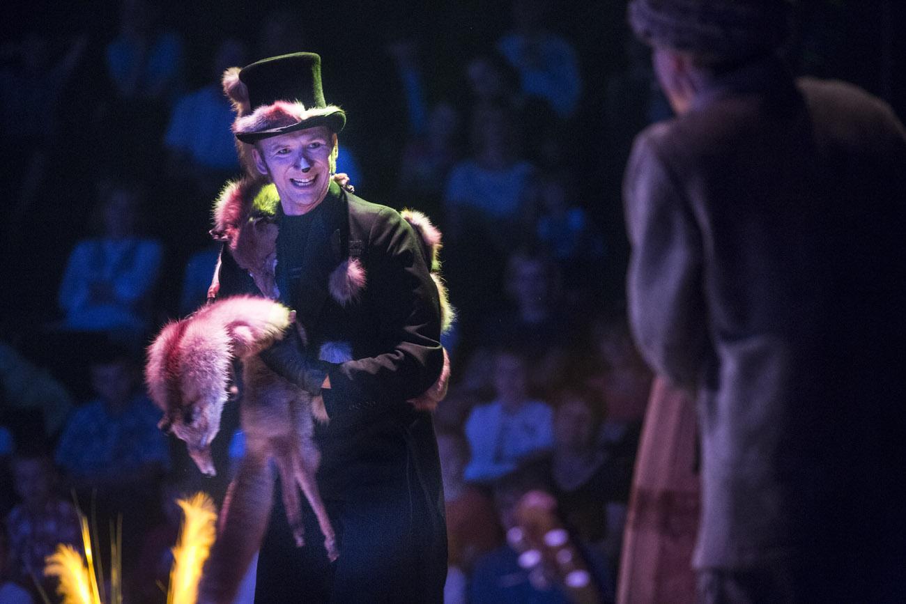 Na pierwszym planie mężczyzna w czarnym garniturze, rękawiczkach i cylindrze. Na barku ma przewieszonego lisa. W rękach również trzyma dużego lisa. W tle widownia w półmroku.