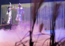 Na drewnianej kładce mężczyzna i kobieta ubrani w białe kostiumy. Trzymają złączone ręcę uniesione do góry. W tle biała zasłona.