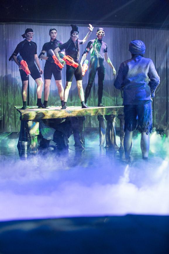 Na scenie , w wodzie, drewniana kładka. Na niej kobieta, w czarnym kombinezonie i pióropuszem na głowie. Obok niej, trzech mężczyzn, w czarnych kombinezonach . Wszyscy trzymają plastikowe, duże pistolety.