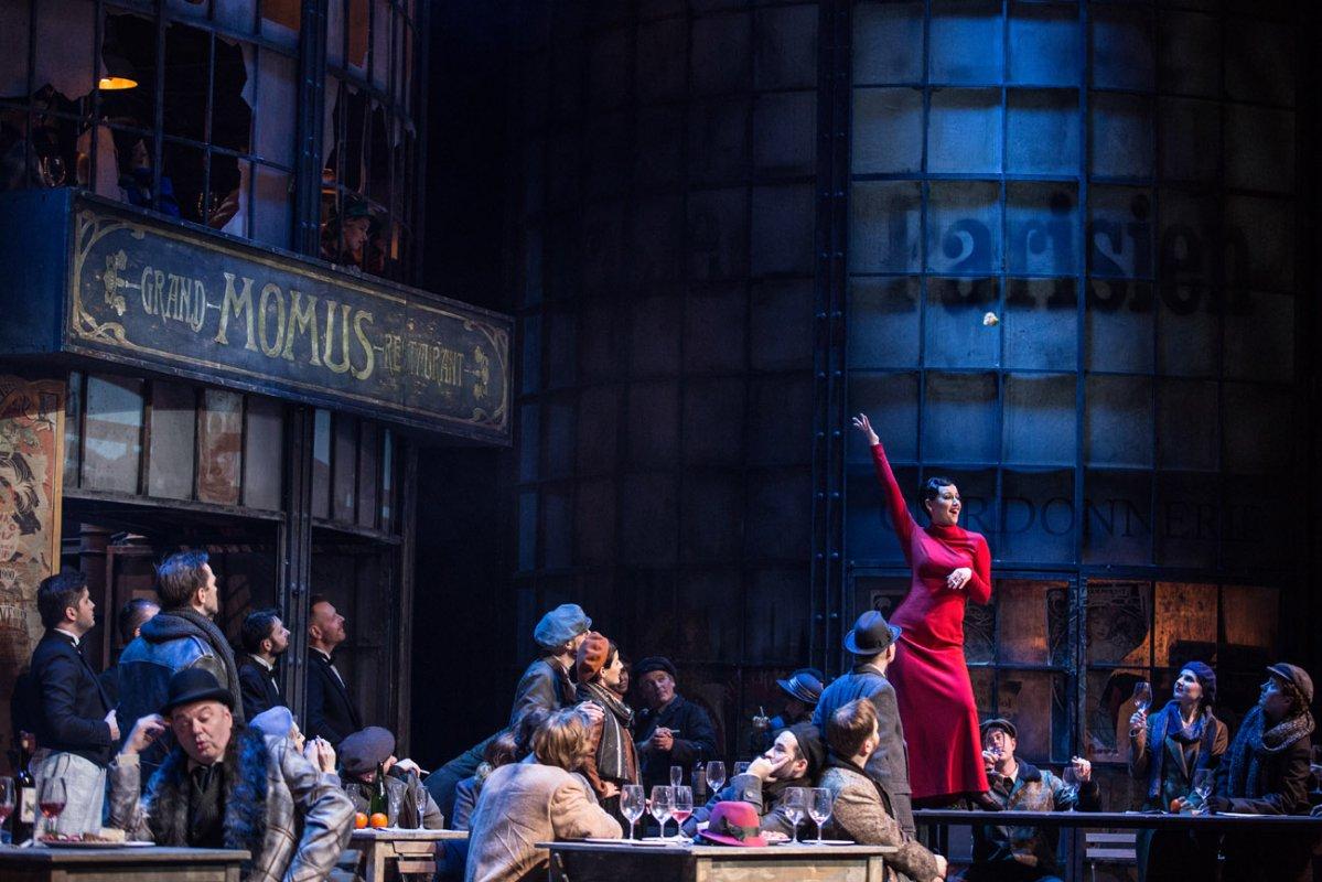 Na scenie kilkanaście osób, część z nich siedzi przy stołach, część stoi.Na stołach stoją kieliszki, na kilku stołach wina.Na jednym ze stołów stoi kobieta w czerwonej , długiej sukni. Z ręką wyprostowaną do góry. Po lewej stronie szyld , na nim napis: '' Grand Momus Restaurant.''