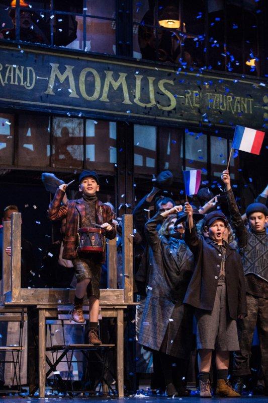 """Na krześle, przed stołem, stoi chłopiec z zawieszonym na szyi bębenkiem. Obok, po prawej stronie grupa osób śpiewa, trzymając francuskie flagi w rękach podniesionych do góry. Za nimi restauracja o nazwie: ''Momus"""""""