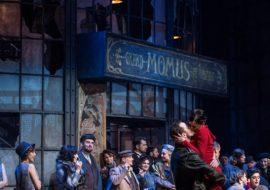 Po lewej duży stół, na nim wino, dwa kieliszki, półmisek. Na środku mężczyzna, trzyma kobietę na rękach. Za nimi grupa kobiet i mężczyzn. Dalej szklana witryna, z częściowo wybitymi szybami. Na środku napis: ''Grand Momus Restaurant''.