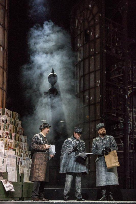 Na scenie trzech mężczyzn. Dwaj ubrani w szare płaszcze, szare czapki. Jeden z nich trzyma białą, dużą kartkę. Drugi - papierową torbę. Mężczyzna obok trzyma