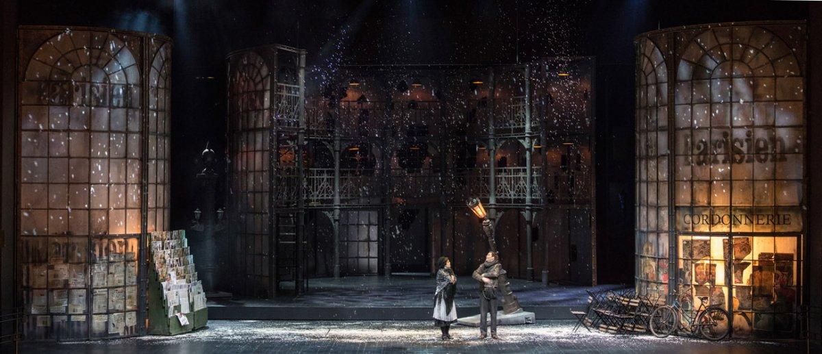 Scena pokazuje uliczkę nocą. Dookoła duże witryny, w nich światło. Po lewej stonie stoisko z gazetami. Po lewej kilkanaście krzeseł stojących blisko siebie, obok oparty o witrynę rower.Na środku sceny kobieta i mężczyzna. Za nimi pochylona, swiecąca latarnia.