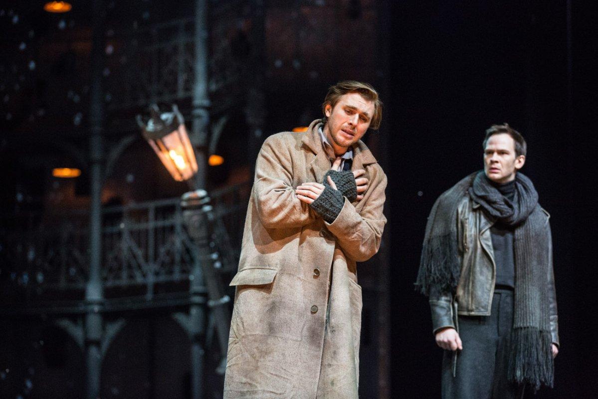 Na pierwszym planie dwóch mężczyzn. Jeden z nich , w przybrudzonym płaszczu, trzyma ręcę skrzyżowane na piersi. Drugi, w skórzane kurtce i szaliku, patrzy w jego stronę. Za nimi pochylona, świecąca latarnia.