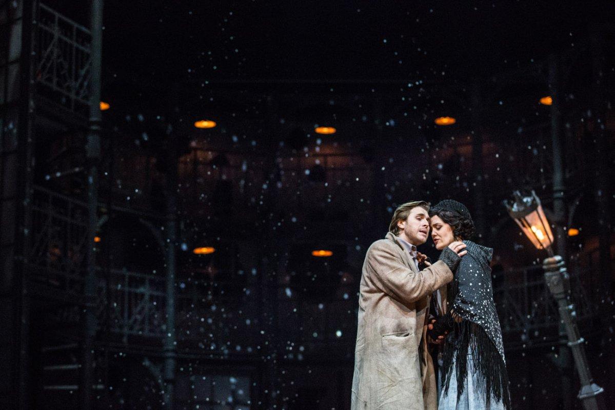 Na pierwszym planie kobieta i mężczyzna stoją blisko, zwróceni do siebie. Mężczyzna trzyma rękę na ramieniu kobiety. Za nimi pochylona, świecąca latarnia. W oddali widać świecące punkty i spadający, sztuczny śnieg.