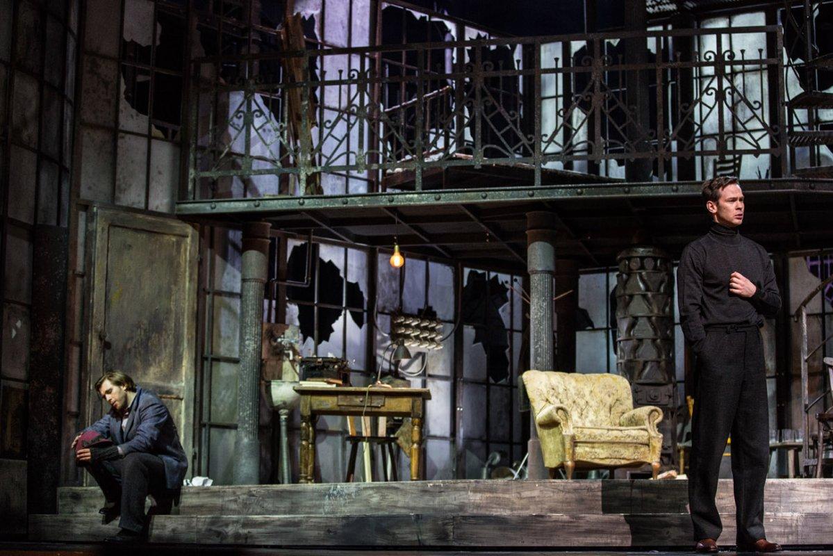 Scena podzielona na parter i piętro. Na dole, na schodach , dwóch mężczyzn. Jeden siedzi