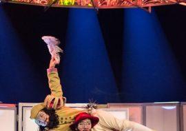 Na scenie dwóch mężczyzn. Jeden w kolorowym fraku, czerwonym kapeluszu i plecionej masce na oczach. trzyma na ramionach, leżącego wzdłuż, mężczyznę w żółtym fraku i białych spodnich. Mężczyzna trzyma w wyprostowanej do góry ręce długie pióro. Za nimi biały parawan. Nad nimi konstrukcja w kształcie koła.