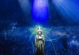 Scena oświetlona niebieskim światłem. Na środku kobieta w długiej sukni.